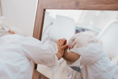 little boy playing with mirror